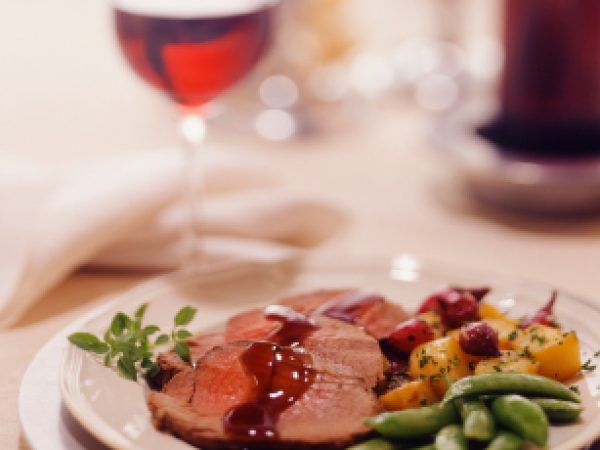 Elegant plate of beef tenderloin, with roast potatoes, shallots, and sugar snap peas. Red wine in background, shallow focus.